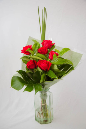 For Valentines Day - Red roses delivered in a vase , with lush green foliage