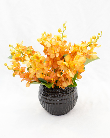 Orchids arranged in low black vase