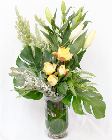 Arrangement tall glass vase with roses and seasonal flowers