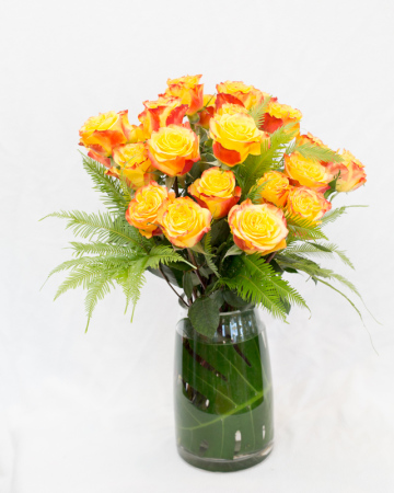 25 Columbian roses in vase with tropical foliage